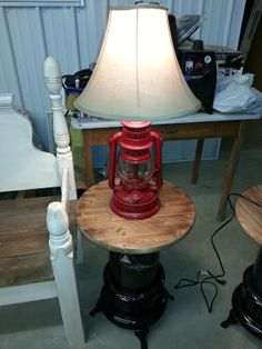 old latern turned into lamp, sitting on a table made out of an old kerosene heater...