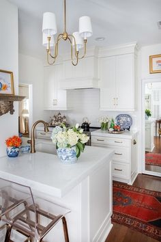 This kitchen may be on the tiny side, but it's packed with upgrades, starting with new cabinetry that spans to the ceiling. Marble countertops are a substantial four inches thick, and the new range hood is also bigger (yet understated). Gold accents and a bold red Oriental runner make this white kitchen anything but plain.