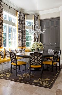 Lovely dining area! Love the pattern of the fabric and the pop of yellow. Great details!! Great grey paint color on built-in cabinets!!