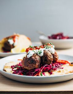 Exceptionally delicious merguez meatball flatbreads layered with red cabbage slaw, herbed yogurt, and harissa.
