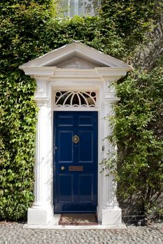 The front exterior of this house is covered with foliage. It is a Roman style main entrance that has two white columns. It has a blue front door with a transom above it and a brown doormat in front of it. The front door has a brass doorknob with a mail slot beside it. The door also features a door bell, a sculpted lion door knocker, and a peephole below it.