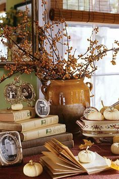 Autumn berries in a crock with books and family photos