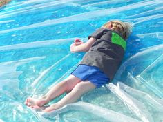 giant outdoor waterbed - Fold a plastic tarp in half and seal all sides with Duct tape, leaving a small hole for hose. Fill with water from the hose. Add food coloring, if desired. We're so going to have to do this in the summer!