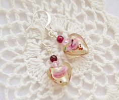 These heart earrings are dainty dangles made of Czech fused glass hearts that are silver foil-lined and floral. They also have genuine