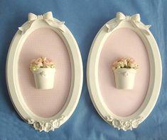 Par de quadros ovais com aplicação de tecidos, peças de resinas e flores. Moldura laqueada. R$ 150,00