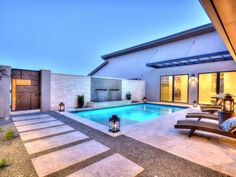 Stone steps lead from the artsy copper gate through a bed of natural rock in this stylish backyard. Stone tile flooring surrounds the lit swimming pool and wicker lounge chairs. A double waterfall feature draws the eye to the far stone wall.