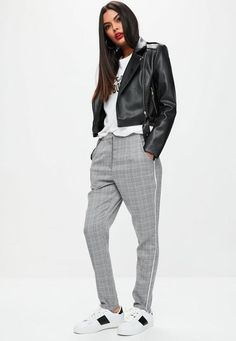 Grey cigarette pants with a Prince of Wales print, pockets, a white trim on the side and stirrup style.