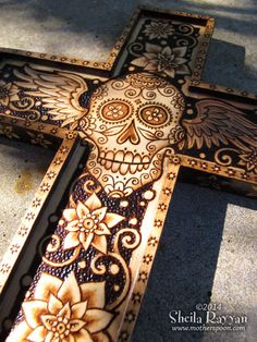 Wooden cross, 6.5x9 with hanger on back. Sugar skull with wings and flowers design was burned on with pyrography pens, then several coats of varnish