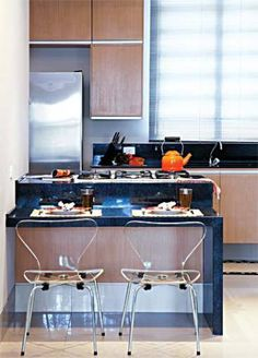 A disposição do fogão, da geladeira e da pia forma um triângulo, o que torna este espaço prático. Na bancada de granito preto são gabriel, duas alturas distintas servem a propósitos diferentes: usado por quem está de pé, o fogão cooktop fica ergonomicamente a 94 cm do chão. Já a área de refeições tem 72 cm – medida exata para a dupla de cadeiras. Projeto de Maurício Karam e Karin Ricciardi.