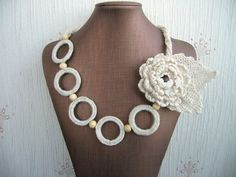 Crochet Linen necklace  http://www.etsy.com/shop/CraftsbySigita?ref=si_shop.  Without the flower and with darker beads or with a smaller flower. That one is too overwhelming.