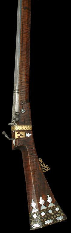 Ottoman matchlock gun, 17th century, two-stage octagonal sighted barrel inlaid with silver arabesques, strapwork and flowerheads along the breech and originally with a silver band around the muzzle, standing single-aperture back-sight inlaid with silver lines, pivoting pan-cover, Circassian walnut stock, 93.7 cm. barrel, a rare surviver of the type captured at the relief of the siege of Vienna in 1683. Most were broken up and the barrels only retained for remounting.