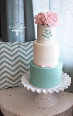 Teal and white wedding cake with pink roses and simple chevron pattern.