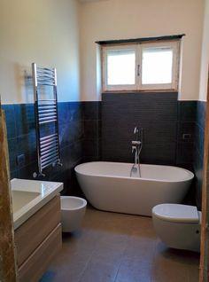 bagno principale con vasca a libera installazione, sanitari sospesi, termoarredo cromato, rivestimento gres porcellanato nero effetto lavagna 30x60, pavimento grigio scuro gres porcellanato 30x60