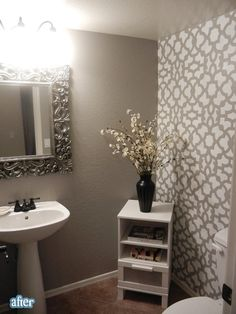 Home Staging: Great Half Bath that has a simple but Luxurious look with the Wall Paper, Mirror and Small Stand with Flowers