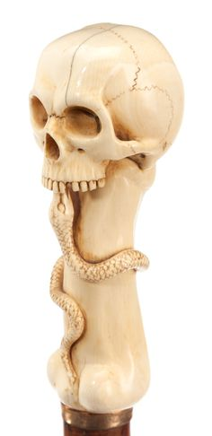 CARVED IVORY SKULL AND SNAKE CANE HANDLE. Circa 1900.