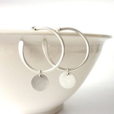 Orbit Hoops Hand crafted from sterling silver. These modern hoop earrings are hand forged with a moveable disc drop on each earring. (Matt & polished finish) Size: 3cm x 4.2cm drop.