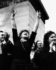 """A Parisian woman gives a triumphant """"V For Victory"""" sign as Allied forces free Paris from German occupation."""