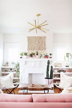 Pink couch for trendy living room. Macrame wall hanging, white fireplace potted cactus Kacey Musgraves teamed up with Elise Larson of A Beautiful Mess to give her living room a bright, Western-inspired makeover.