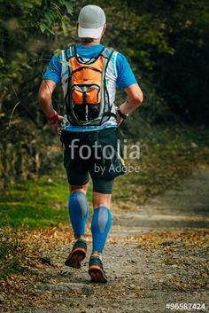 young man in compression socks running through Park. on back of his backpack. autumn landscape, fallen leaves