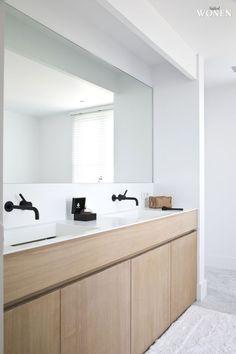 Dunne rand en vormgeving witte wastafel // Houten meubel // Grijze vloer // Grote spiegel
