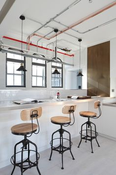 Industrial kitchen with exposed brass piping on the ceiling, wood and metal barstools, brass pendant lighting, white subway tile, and built-in bar bench | Oliver Burns