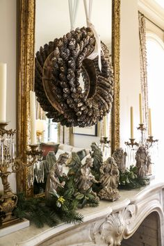 Atop the original antique Carrara marble fireplace mantel in the living room sits a nativity scene handed down by Kyler's mother, Coco Martin. The mirror is decorated for the season with a simple suspended pinecone wreath.