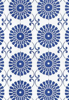 An embroidered curtain fabric featuring a large stylised sun design printed in blue with stitched cream detailing on a white linen background.
