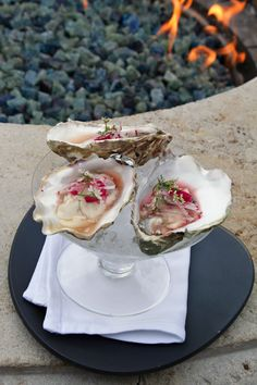 Almost too pretty to eat, The Peninsula's Roof Garden restaurant serves up raw Kumamoto oysters with Mezcal, coriander flower, & pickled onions by their rooftop fire pit.