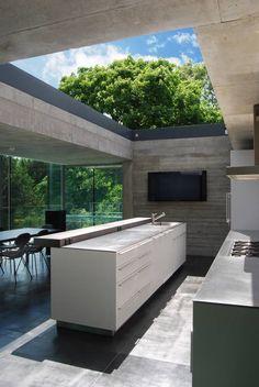Kitchen with sliding rooflight to create open-air court : Minimalist kitchen by Eldridge London