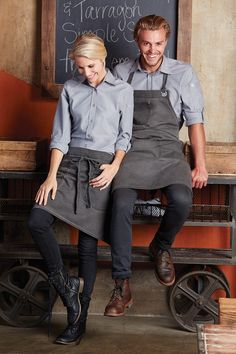 The New Chambray Shirts come in 4 colours; Dusty Rose, Ecru, Green Mist and Grey. Available in Male and Female styles to ensure you get the perfect fit! Cafe Uniform, Waiter Uniform, Hotel Uniform, Kellner Uniform, Bartender Uniform, Chef Dress, Uniform Design, Work Uniforms, Poses