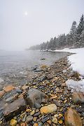 The sun begins to burn through falling snow along the shore of Owls Head, Maine. I got down low to capture the surf washing against the pebble beach.