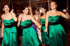 Emerald green tea-length satin bridesmaids dresses featuring sweetheart necklines and black satin sashes - Photo by Kara