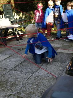 Dan gaan we door naar buiten. Een bolletje rood wol en een paar tuinstoelen en je hebt deze gave lasergame genaamd Superlaser! De superhelden moeten eronderdoor en eroverheen om aan de overkant te komen. Je mag de lasers niet aanraken.