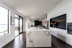 The kitchen features large windows, wood floors and a marble kitchen island