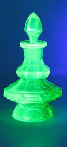 A pagoda shape Vaseline uranium cut glass dressing table bottle with a facet spire stopper and double skirt facet body on a rounded eight sided foot, the under-base is embellished with cut fans and cross hatching.