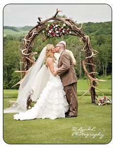 Gorgeous couple, flowing, romantic veil with rustic outdoor archway.  Photo D'LyndL Photography www.dlyndlphotography.com