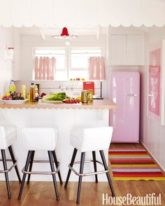 Designer Krista Ewart add scalloped lights for a kitschy accent in this Balboa Island beach house kitchen, (plus, they match the curvy detail on the counter and the molding).