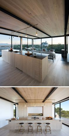 On the upper level of this home there's the living, dining and kitchen area. A large kitchen island with plenty of storage divides the space. On the right, a wood burning stove sits on a suspended steel shelf.