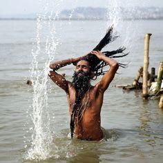 """Un """"naga sadhu"""", un asceta induista, immerso nell'acqua considerata sacra di Sangam, il punto di confluenza di tre fiumi - il Gange, lo Yamuna e il Saraswati - durante una celebrazione che si tiene ogni anno a Allahabad, in #India"""
