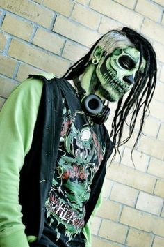 Dreadlocks, shaved side, and awesome makeup.