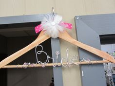 Look at this adorable hanger with Bride on it. Perfect for the bride to hang her wedding dress on it for pictures! Get them with the bridesmaids names or with the brides future last name. #hanger #bride #soontobemrs #cute #wedding #pictureideas #pinkys #pinkysplace