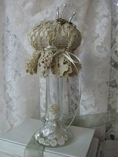 Pin cushions made on vintage glass vase.  Notice the buttons in the vase, and the vintage doily top!