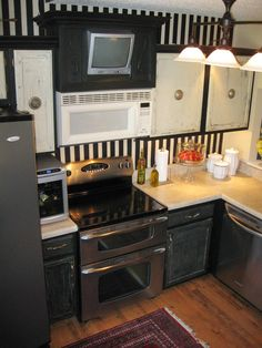 Black and white distressed kitchen - notice the different textures...the base is solid black, crackle black on the bottom cabinets and distressed white on the top. I PERSONALLY do not like the striped wallpaper.