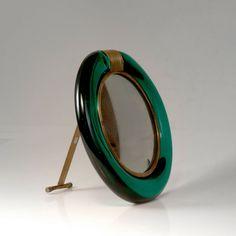 Flavio Poli. Table mirror, c1950. D. 28.8 cm. Made by Seguso Vetri d'Arte. Green glass, brass sheet, plate glass. Marked: Seguso VETRI D'ARTE MURANO.