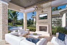 A stacked stone #fireplace is the focal point of a #transitional Florida home's #outdoor seating area.