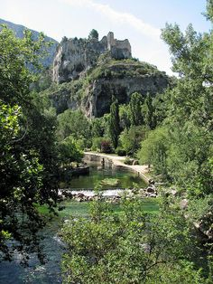 An ancient castle sits on a mountaintop, overlooking the village of Fontaine de Vaucluse, France.