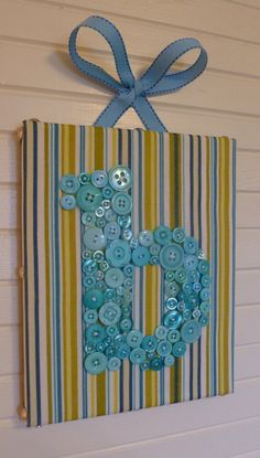 Cute for wedding or baby shower gift. Or, heck, for yourself! I would glue the buttons onto a fabric wrapped canvas. You can dye or spray paint plain white plastic buttons. Ocean Blue Button Monogram on 8x10 Canvas -- by Letter Perfect Designs,via Etsy.