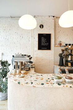 modern interior of coffee cafe Synonym in hamilton, canada with terrazzo countertops and painted brick walls. Cafe Shop Design, Coffee Shop Interior Design, Bakery Interior Design, Coffee Cafe Interior, Brewery Interior, Small Cafe Design, Interior Shop, Coffee Design, Deco Restaurant