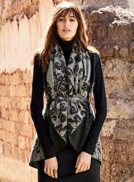 Winter's coziest layer is a striking statement piece as well. Double jacquard knit of felted baby alpaca (70%) and wool (30%), the grey and charcoal cocoon vest showcases large-scale florals from a Russian folk painting. Detailed with an exaggerated shawl collar, deep back pleat and blanket-stitched trim. Gorgeous belted or left to float free.