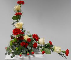 Asymmetrical arrangement, red roses and carnations